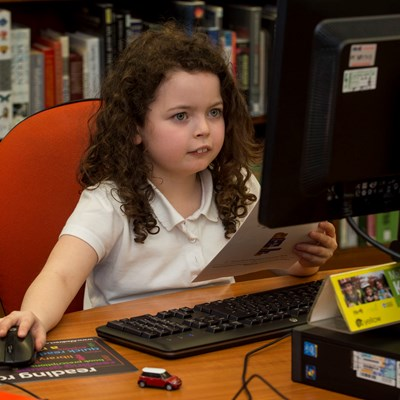 Girl sitting coding at a computer during a Code Club session At Kirkcaldy Library in Fife