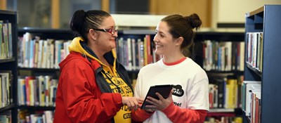 A Digi-Pal Volunteer from Glasgow Libraries talks to a library user at Bridgeton Library in Glasgow