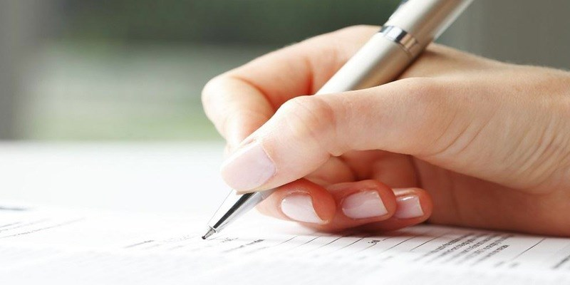 Close up image of a woman filling out a form in pen.
