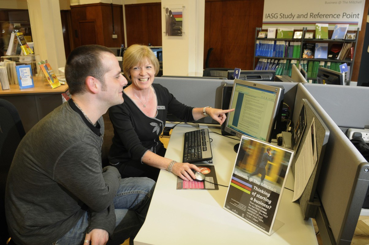 Lady shows library user how to use the computer at the Business Hub in The Mitchell Library in Glasgow